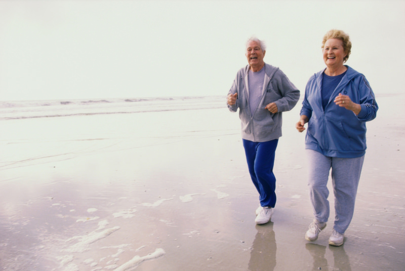 Elderly couple running on beach